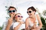 60923369-padres-jóvenes-con-su-pequeño-hijo-en-gafas-de-sol-coloridos-comer-el-helado-jardín-soleado-de-verano